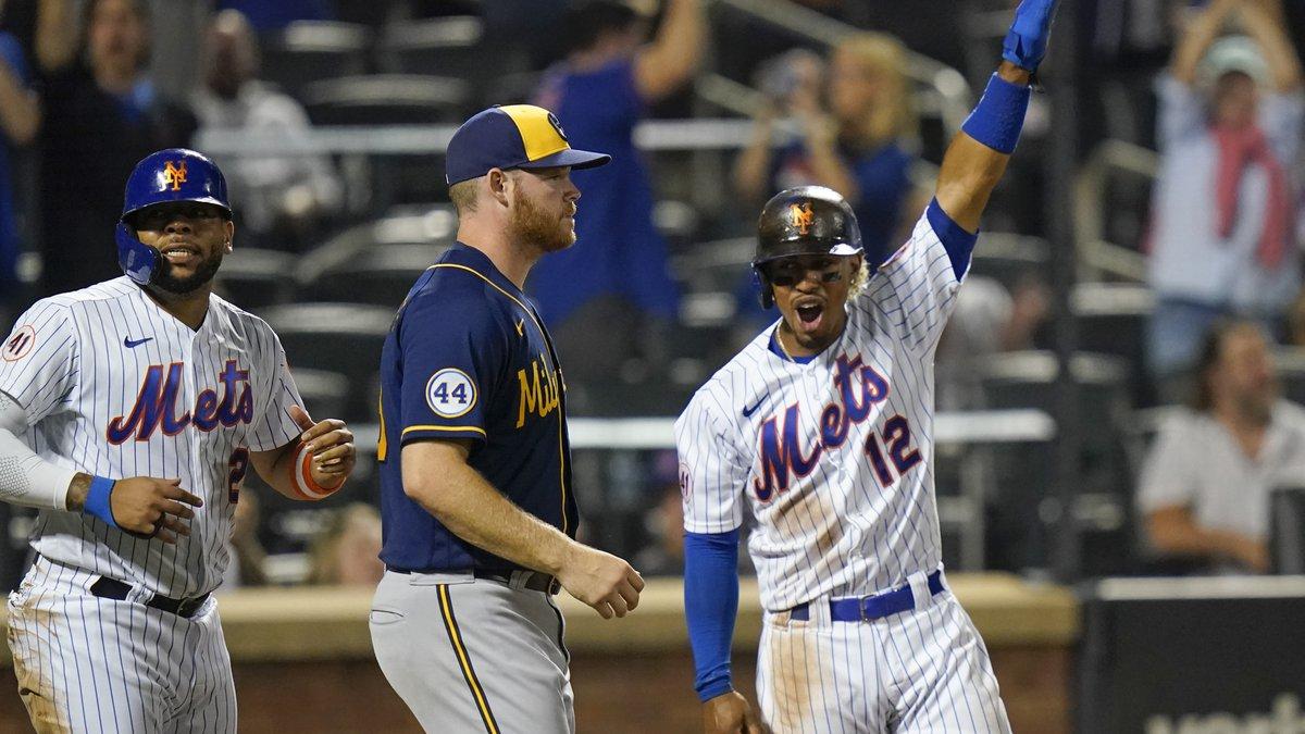 Milwaukee Brewers starting pitcher Brandon Woodruff, center, reacts as New York Mets' Francisco...