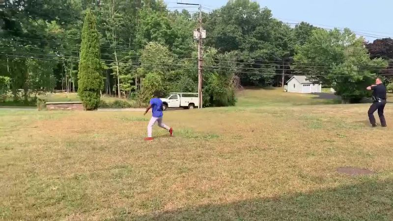 Officer Tyler McElman stops while on patrol to play football with a young boy who was playing...