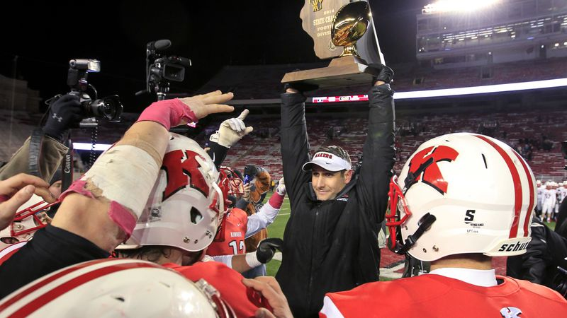 Kimberly coach Steve Jones raises the WIAA Division 1 championship trophy in celebration after...