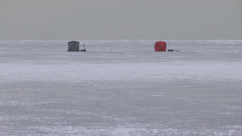 Two portable ice shanties off the shore of the bay near Red River County Park