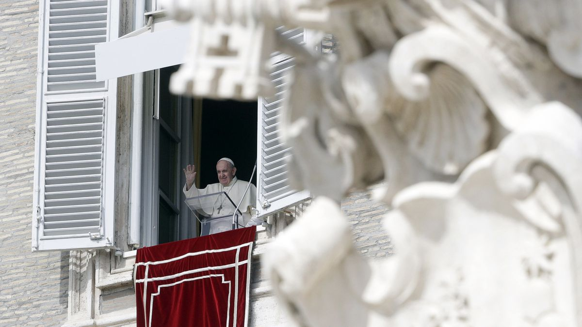 Pope Francis waves during the Angelus noon prayer delivered from his studio window overlooking...