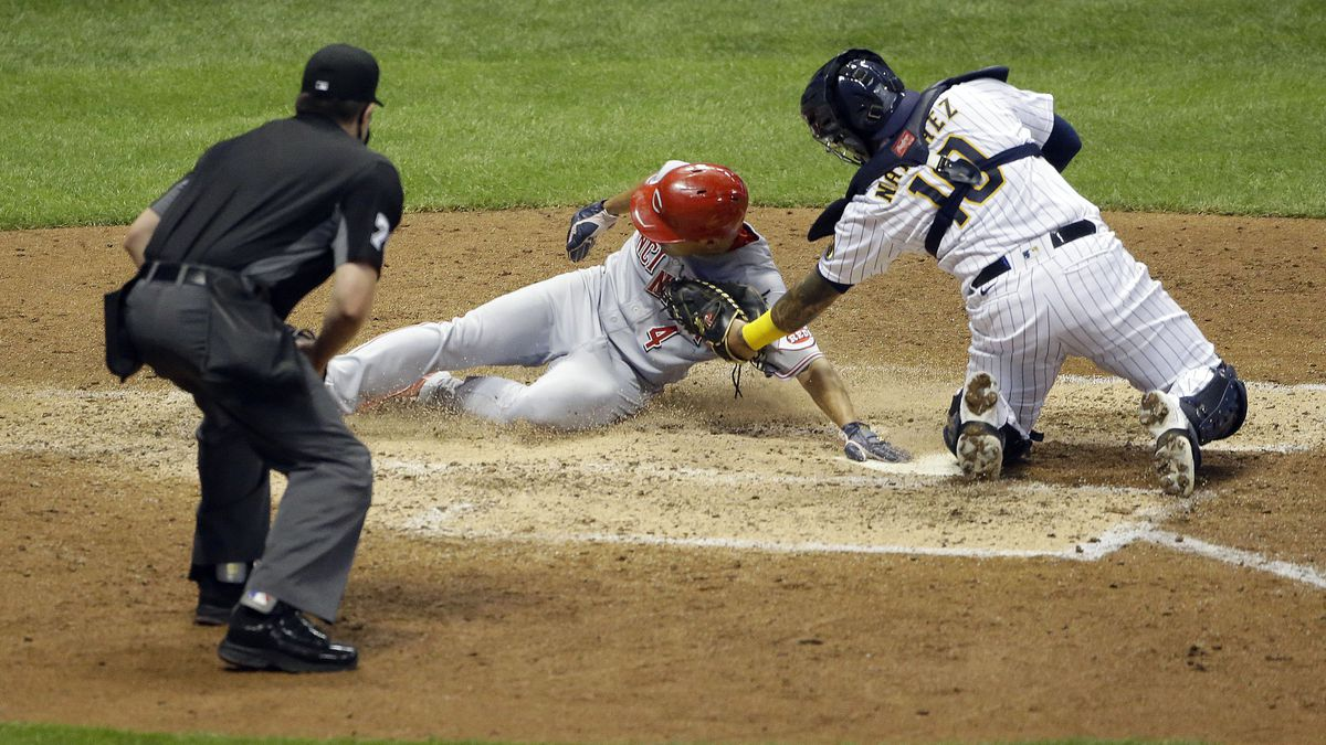 Cincinnati Reds' Shogo Akiyama (4) slides in safely at home past the tag of Milwaukee Brewers' Omar Narvaez during the fifth inning of the second baseball game of a doubleheader Thursday, Aug. 27, 2020, in Milwaukee. (AP Photo/Aaron Gash)