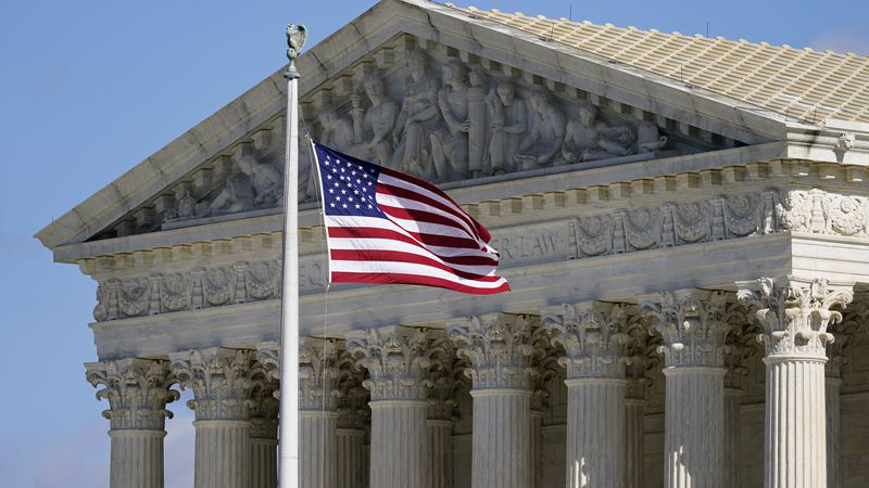 FILE - In this Nov. 2, 2020, file photo an American flag waves in front of the Supreme Court...