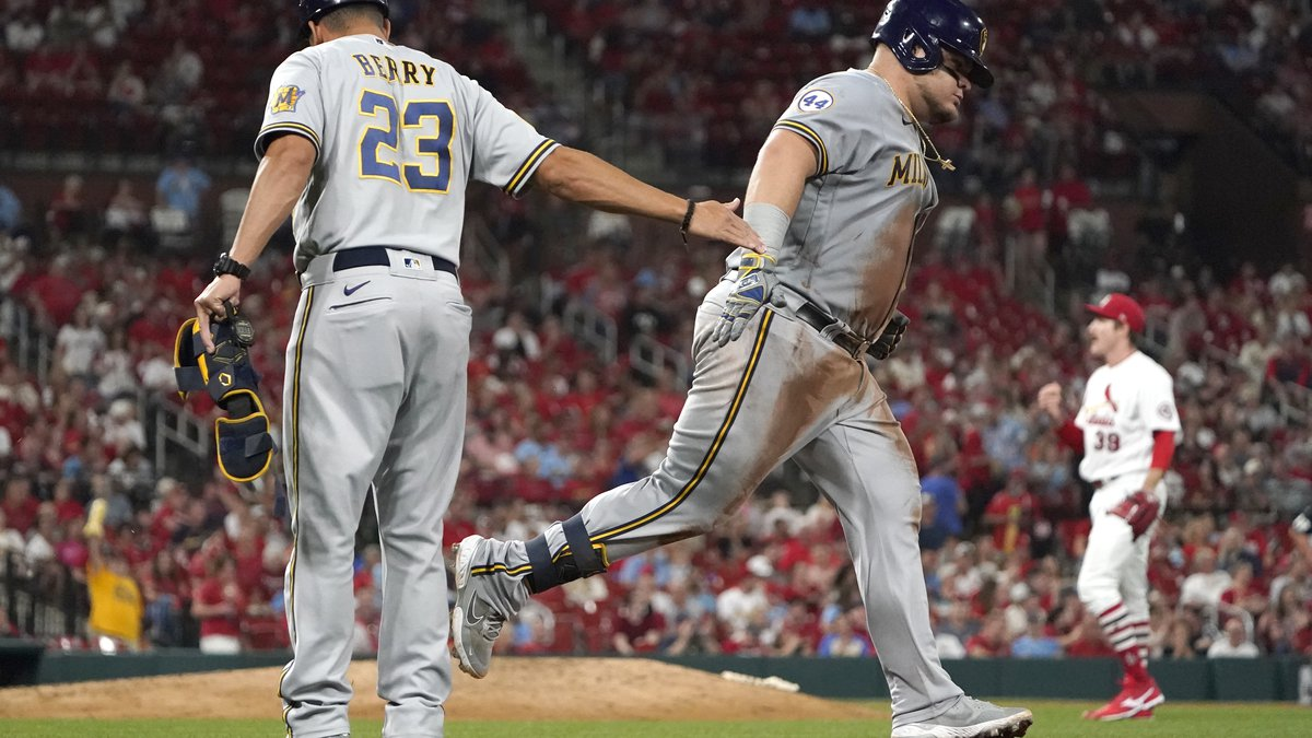 Milwaukee Brewers' Daniel Vogelbach is congratulated by first base coach Quintin Berry (23)...