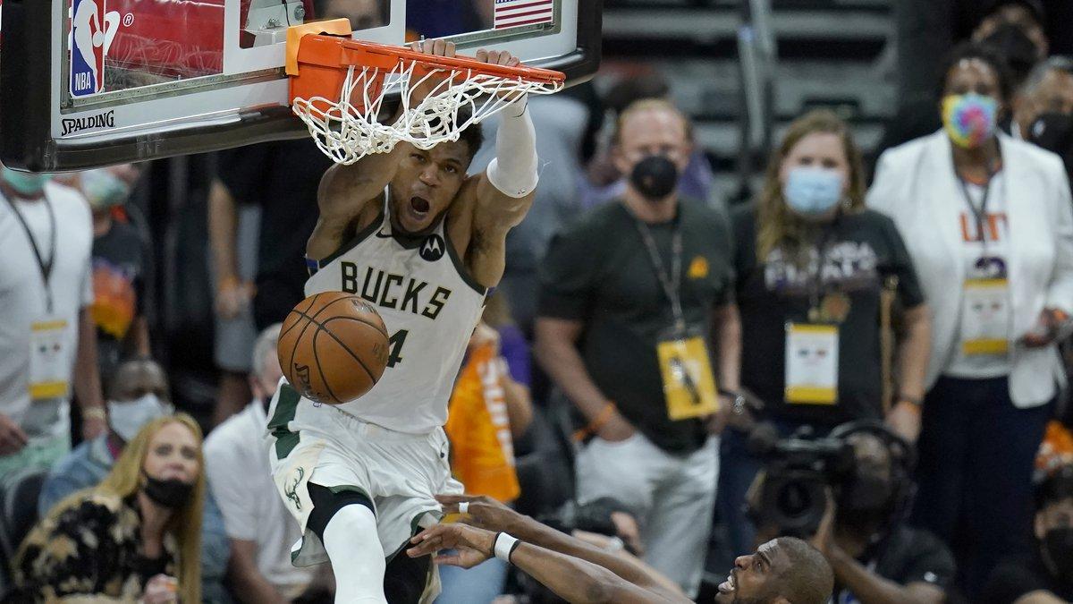 Milwaukee Bucks forward Giannis Antetokounmpo, top, dunks over Phoenix Suns guard Chris Paul...