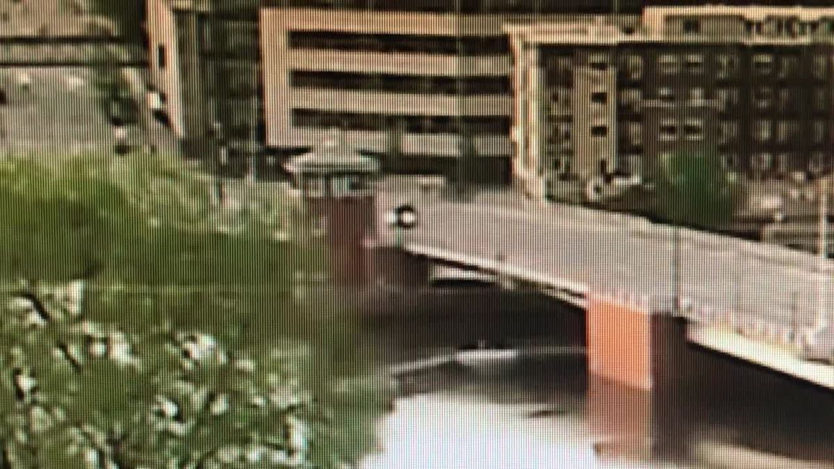 A car swerving on the Main Street Bridge in Green Bay hit a guardrail, throwing a passenger into the Fox River (screenshot from video captured by Titletown Brewing Company camera)