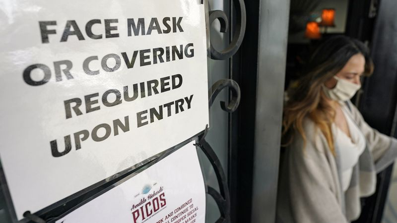 A sign asking customers to wear a face covering is displayed at the entrance to Picos...