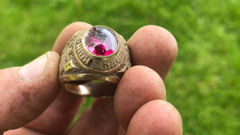 Mike Counter hold a 1976 high school class ring he unearthed while metal detecting.