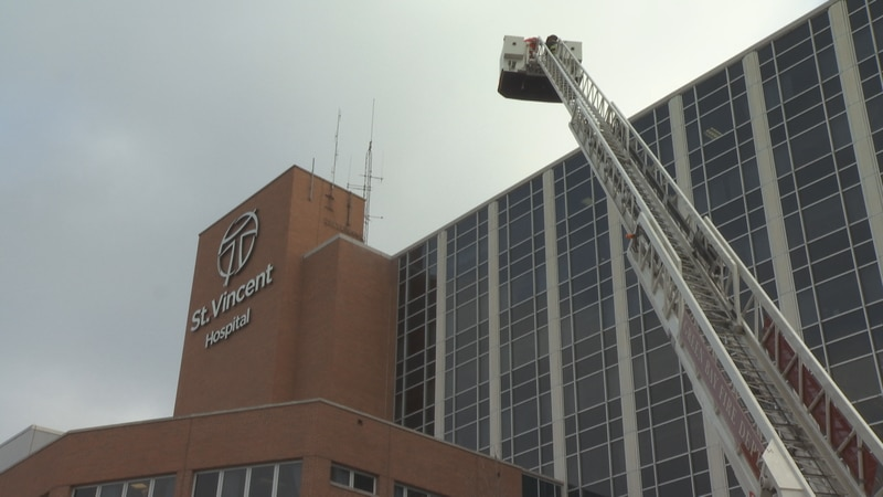 Santa joins a Green Bay Metro firefighter high in the air outside the hospital to wave to...