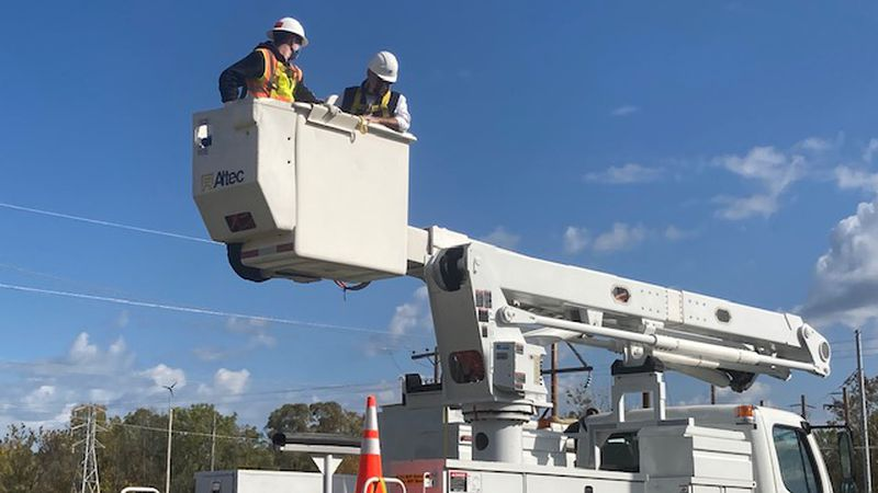 U.S. Secretary of Energy Dan Brouillette (pictured right) rides in a bucket truck during a...