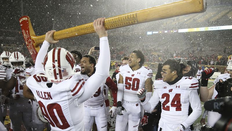 Wisconsin punter Connor Allen (90) holds up Paul Bunyan's Axe during the post game celebration...