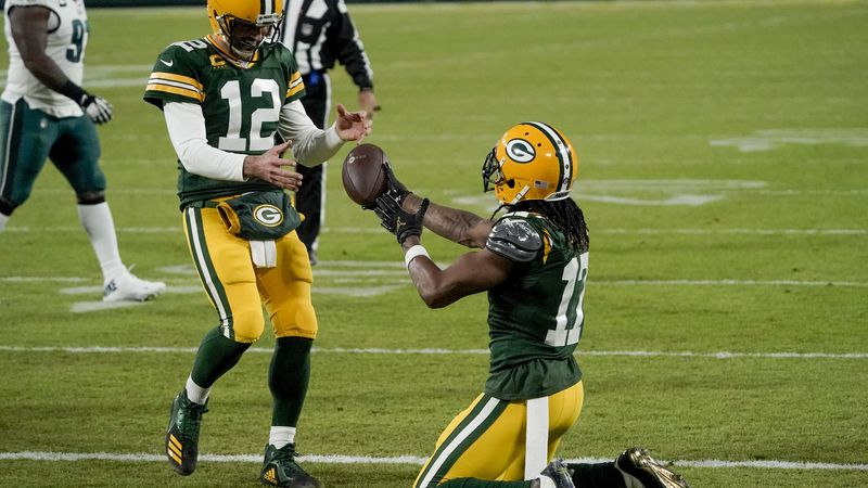 Green Bay Packers' Davante Adams hands the ball to quarterback Aaron Rodgers after catching a...