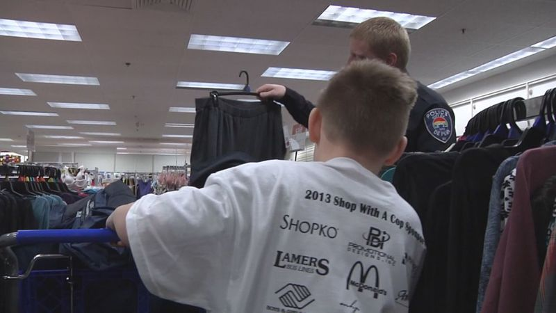 A De Pere Police officer helps a child pick out Christmas gifts as part of the annual Shop with...