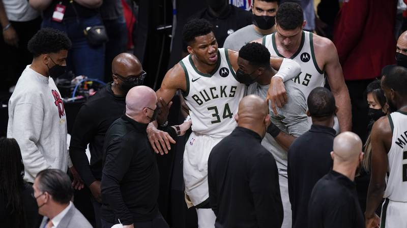 Milwaukee Bucks' Giannis Antetokounmpo (34) is helped off the court after he and Atlanta Hawks'...