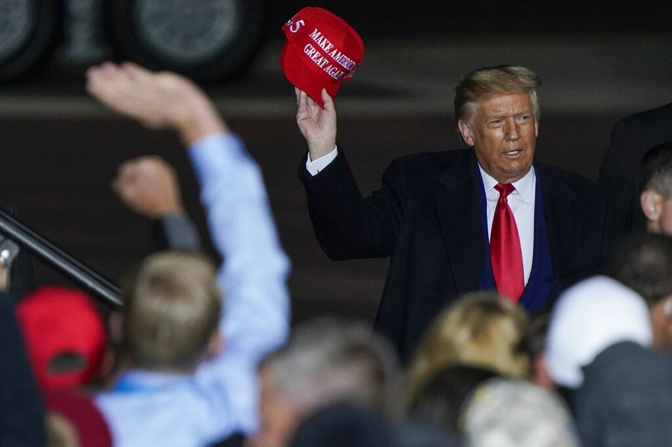 In this Sept. 17, 2020 file photo President Donald Trump throws a hat to the crowd after...