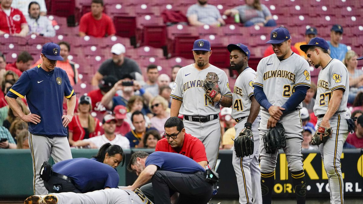 Training staff attend to Milwaukee Brewers' Travis Shaw during the second inning of the team's...