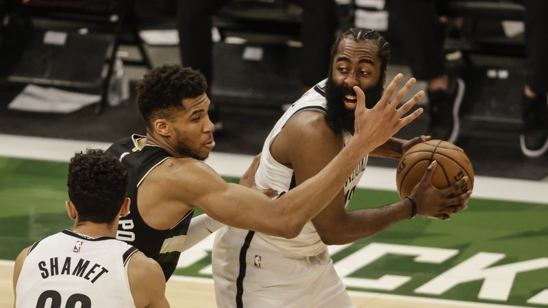 Brooklyn Nets' James Harden, right, is guarded by Milwaukee Bucks forward Giannis...