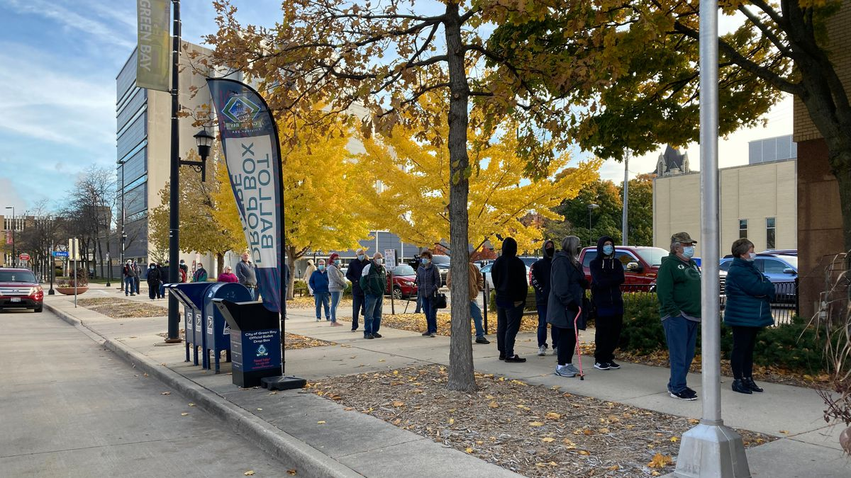 Voters line up outside Green Bay City Hall for the first day of in-person early voting. Oct....