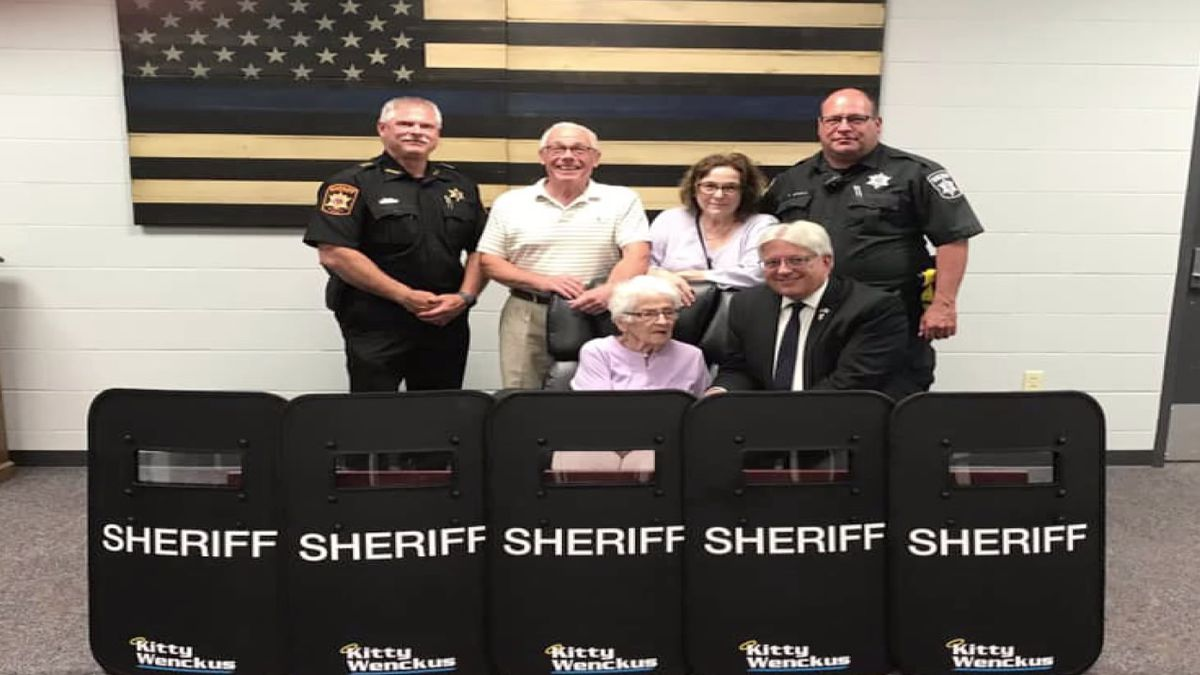 Kitty Wenckus (sitting) and her family with Waupaca County sheriff's officials (photo provided)
