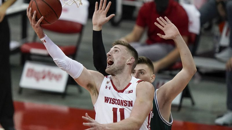 Wisconsin's Micah Potter shoots past Wisconsin-Green Bay's Cem Kirciman during the second half...