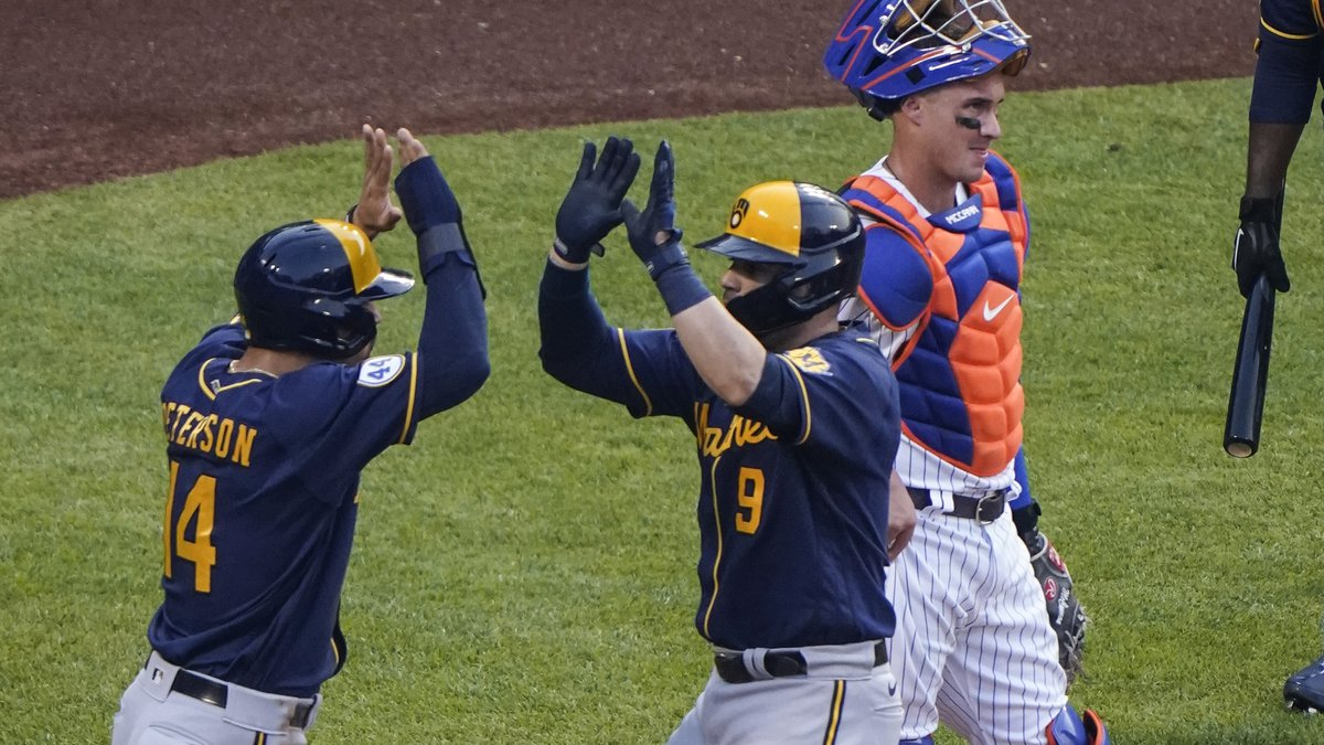 Milwaukee Brewers' Manny Pina, right front, celebrates with Jace Peterson, while New York Mets...