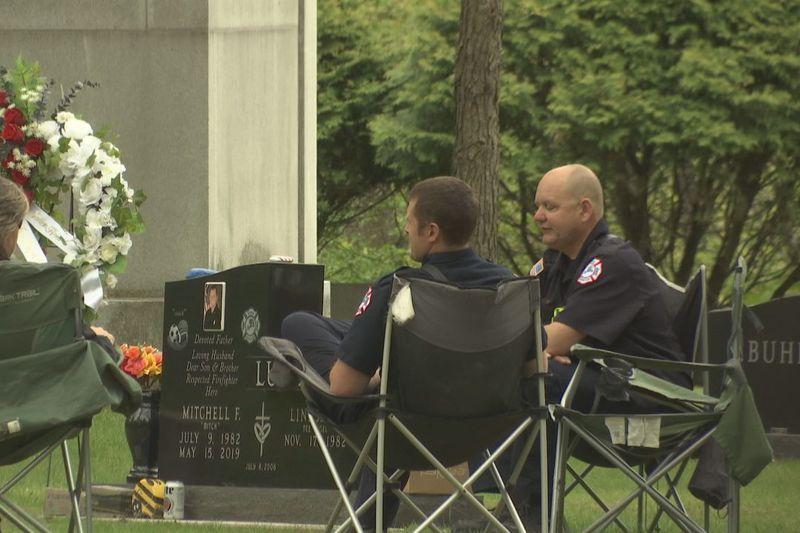 Three Appleton firefighters sat around the gravesite of Mitchell Lundgaard, 36, who was killed...