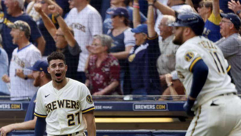 Milwaukee Brewers' Willy Adames(27) reacts to Rowdy Tellez' , right, three-RBI pinch hit home...