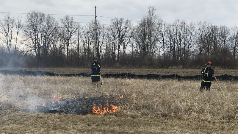 Two Fond du Lac firefighters watch over a brush fire set during a demonstration.