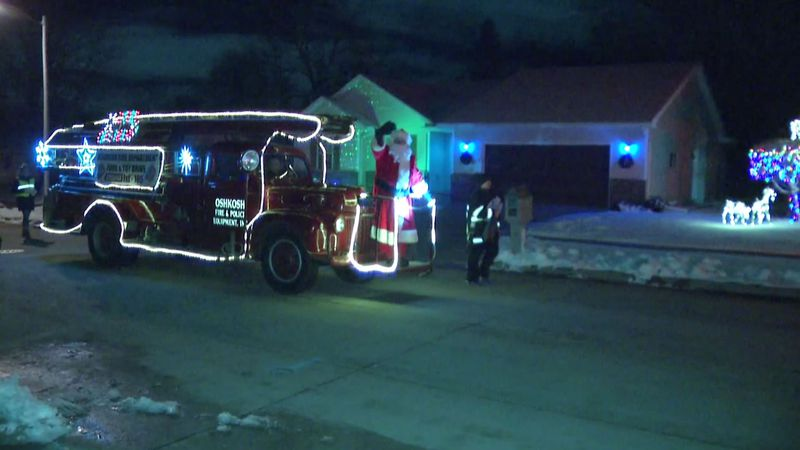 Santa Claus rides into Oshkosh on a vintage fire truck in 2019 to encourage donations of toys...