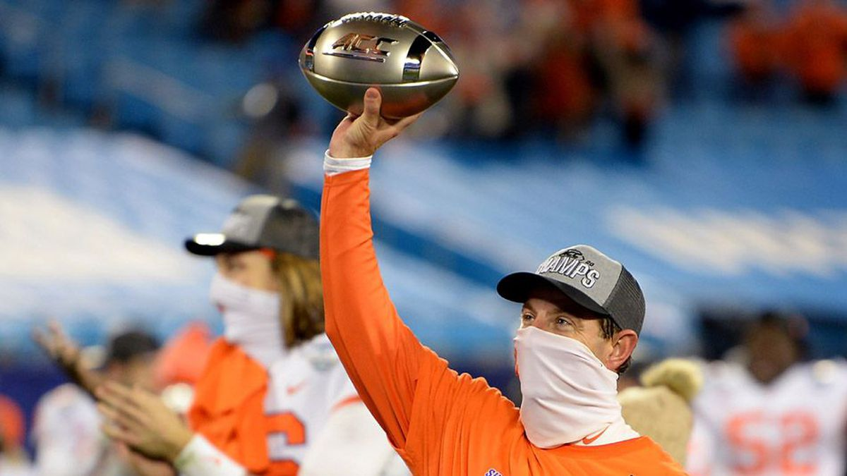 Clemson Tigers head coach Dabo Swinney holds the ACC Championship trophy in the air to the...