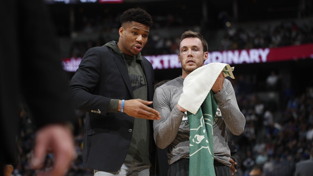 Milwaukee Bucks forward Giannis Antetokounmpo, left, confers with guard Pat Connaughton during a timeout in the first half of an NBA basketball game against the Denver Nuggets, Monday, March 9, 2020, in Denver. (AP Photo/David Zalubowski)