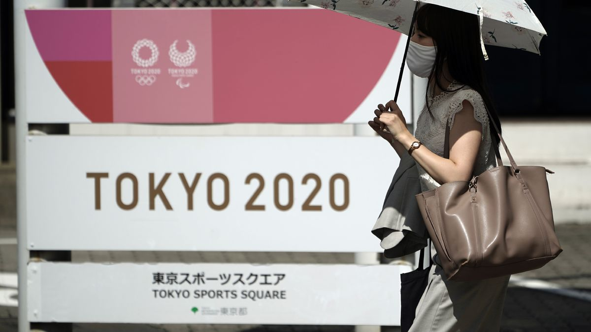 A woman wearing a face mask to help curb the spread of the coronavirus walks in front of Tokyo 2020 sign Friday, Sept. 4, 2020, in Tokyo. The CEO of the Tokyo Olympics Toshiro Mut said Friday that having a vaccine is not a requirement for holding next year Olympics and Paralympics.