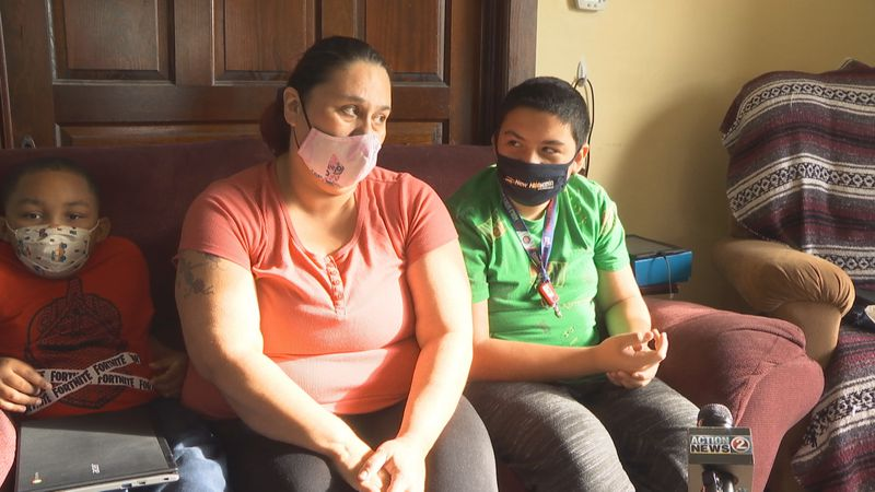 Margarita Ramirez sits on the couch with her 12-year old autistic son and 7-year old grandson.