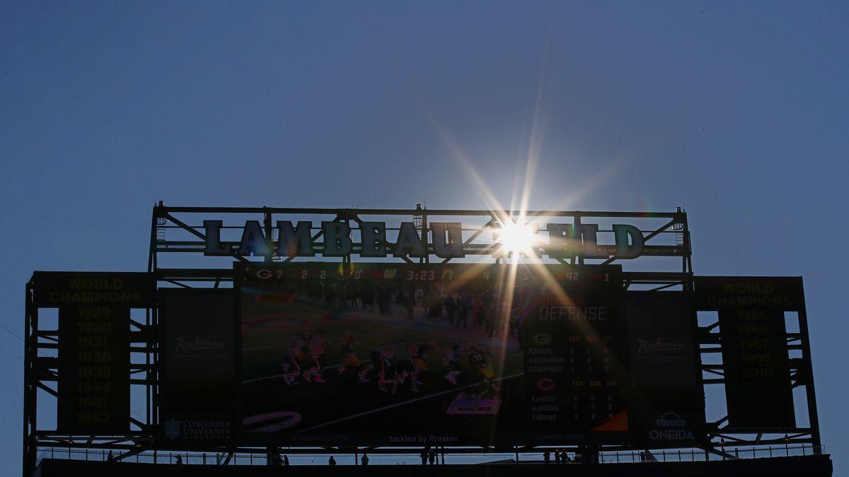 The sun peeks through the scoreboard at Lambeau Field during an NFL football game between the...