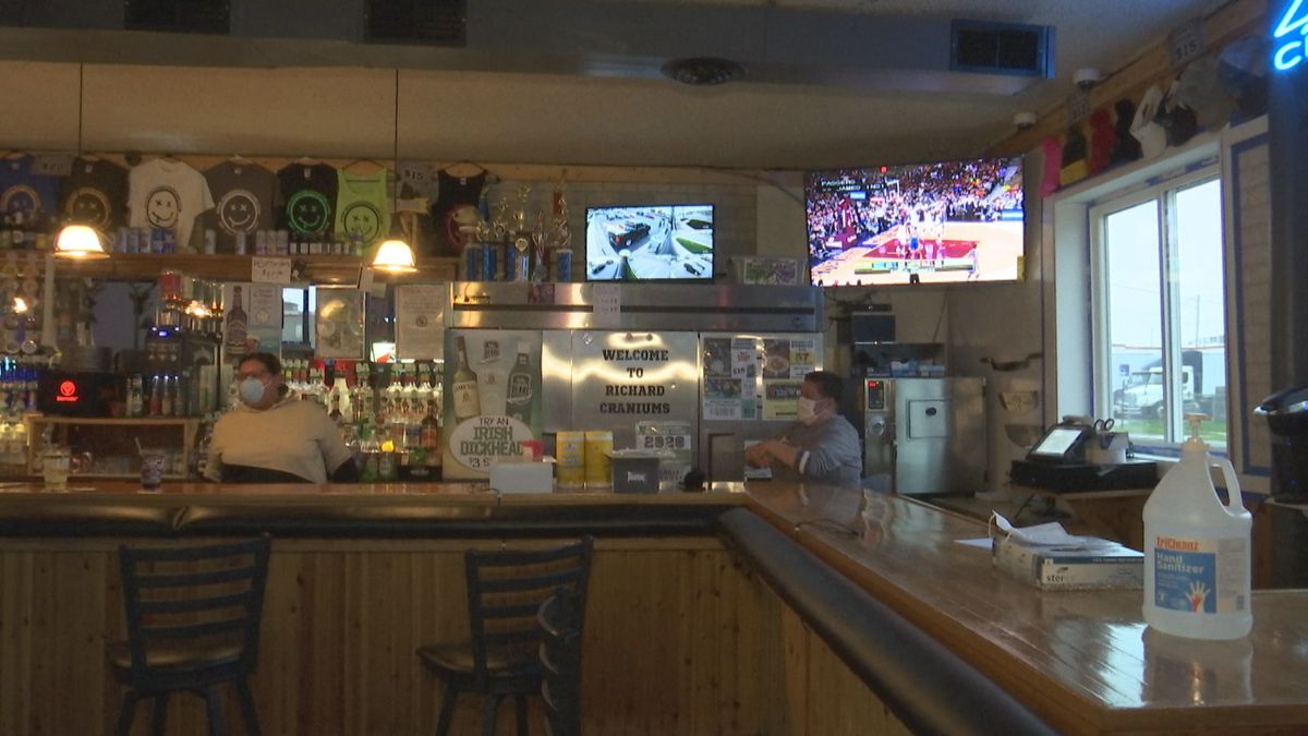 Bartenders at Richard Craniums wear masks after briefly opening after state Supreme Court ruling. The bar later closed after the Brown County Health Department reinstated the Governor's orders.