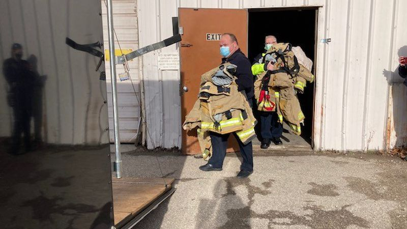 Green Bay Metro and De Pere Firefighters load used turnout gear onto a trailer that will...