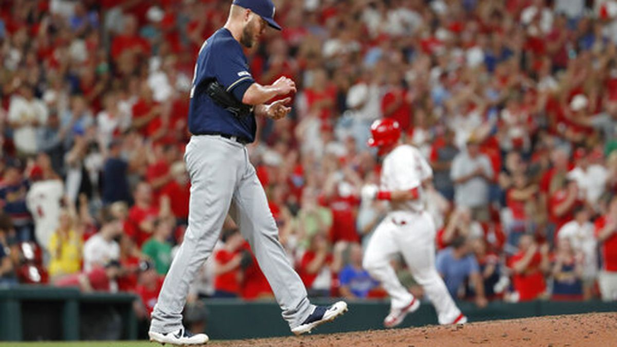 Milwaukee Brewers starting pitcher Jimmy Nelson, left, walks back to the mound after giving up a three-run home run to St. Louis Cardinals' Paul Goldschmidt, back right, during the sixth inning of a baseball game Friday, Sept. 13, 2019, in St. Louis. (AP Photo/Jeff Roberson)