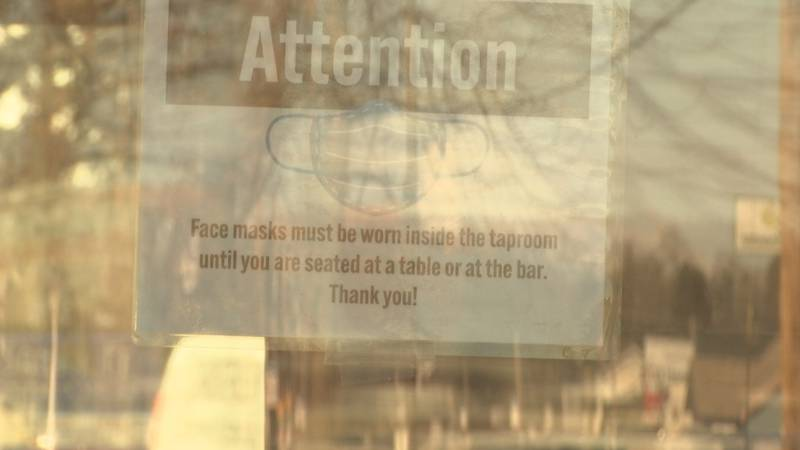 A sign is placed on the front door of Zambaldi Beer in Green Bay telling people to wear masks.