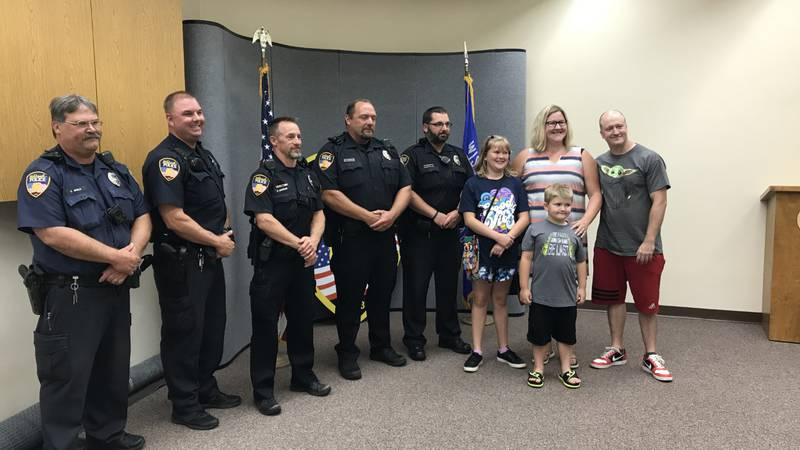 Members of the Stadtmueller family pose for a picture with the Oshkosh Police officers who...