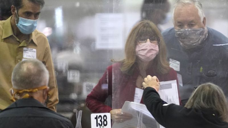 Recount observers check ballots during a Milwaukee hand recount of Presidential votes at the...