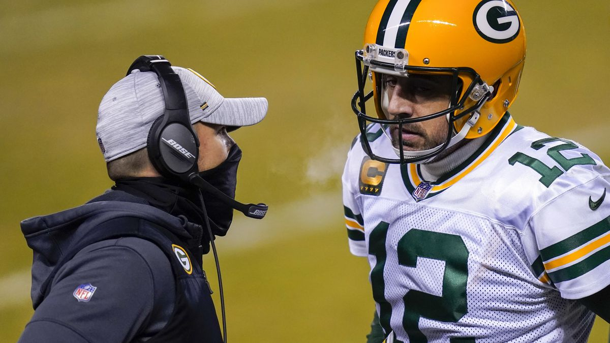 Green Bay Packers head coach Matt LaFleur talks to Aaron Rodgers during the second half of an...