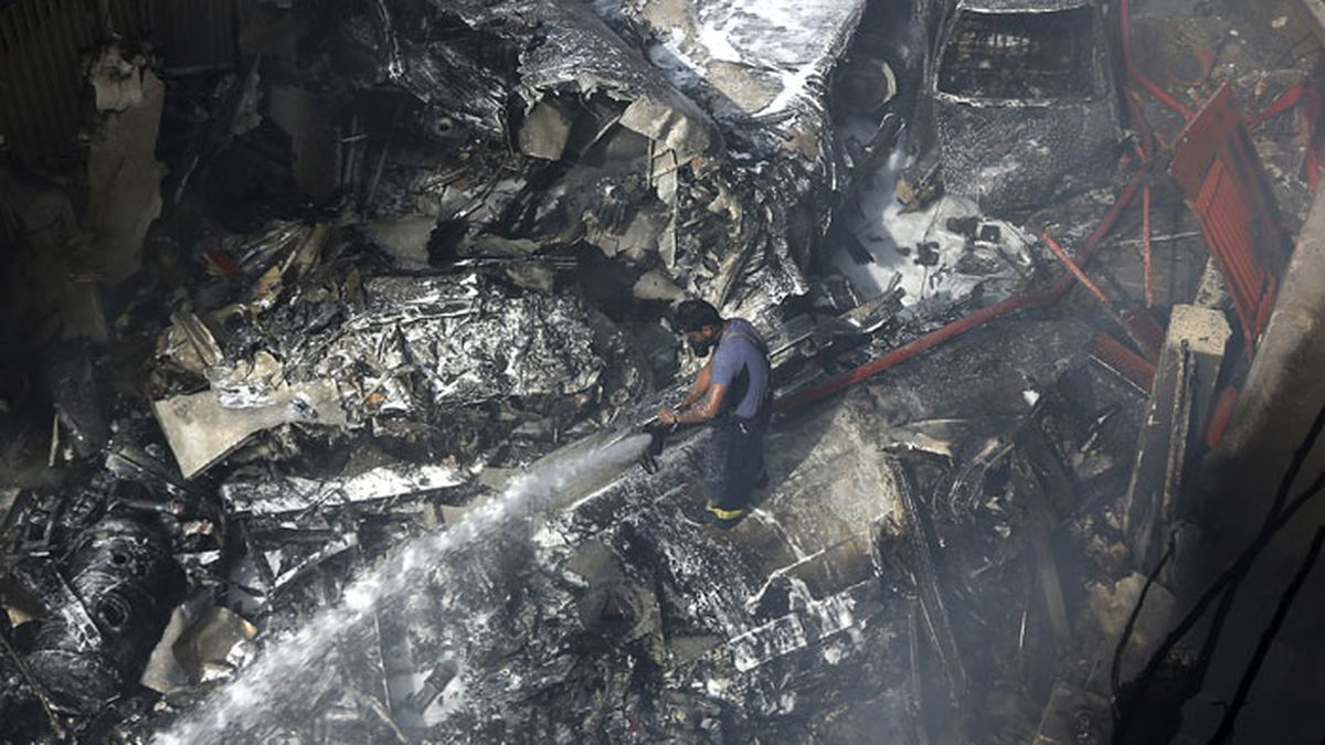A firefighter tries to put out fire caused by plane crash in Karachi, Pakistan, Friday, May 22, 2020. An aviation official says a passenger plane belonging to state-run Pakistan International Airlines carrying more than 100 passengers and crew has crashed near the southern port city of Karachi. (AP Photo/Fareed Khan)