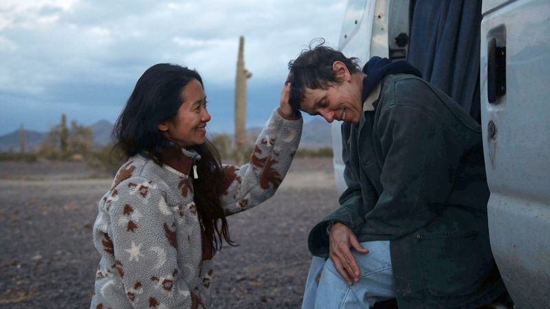 "Director Chloé Zhao, left, appears with actress Frances McDormand on the set of ""Nomadland."""