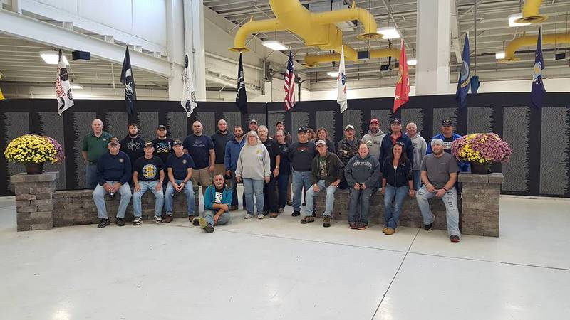 A group poses in front of the Traveling Vietnam Wall on its last trip to Oshkosh in 2016.