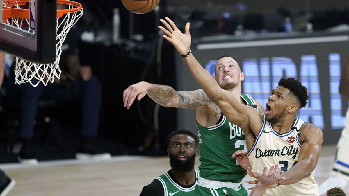 Milwaukee Bucks' Giannis Antetokounmpo, right, heads to the basket as Boston Celtics' Daniel Theis defends during the second half of an NBA basketball game Friday, July 31, 2020, in Lake Buena Vista, Fla. (AP Photo/Ashley Landis, Pool)