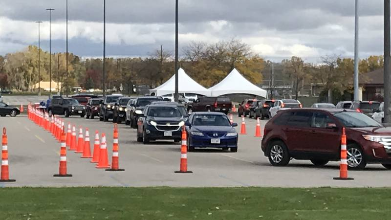 Cars line up on the first day of COVID-19 testing at a new site outside Appleton North High...