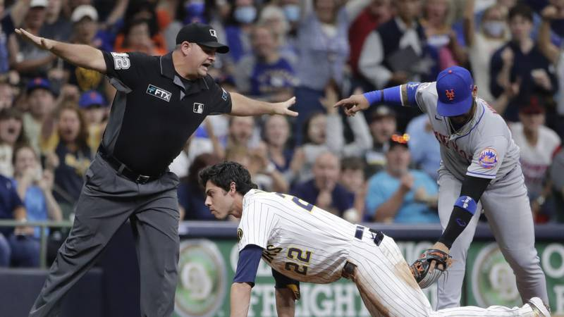 Milwaukee Brewers' Christian Yelich (22) slides safely into third base past the tag of New York...