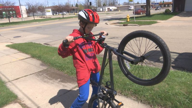 Cayden Parks, 11, received a new bike from Oshkosh firefighters after his old one was ruined...