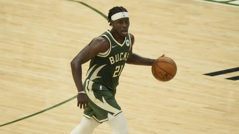 Milwaukee Bucks' Jrue Holiday dribbles during the first half of Game 3 of the NBA Eastern...