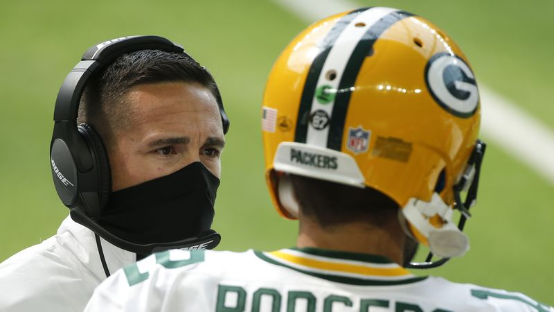 Green Bay Packers head coach Matt LaFleur, left, talks with quarterback Aaron Rodgers (12)...